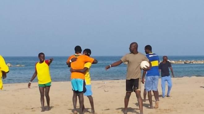 I migranti giocano a calcio in spiaggia