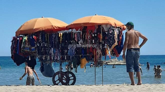 Ambulante spiaggia immigrati venditori costumi invisibilità